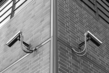 Observation cameras on a building corner in black and white.